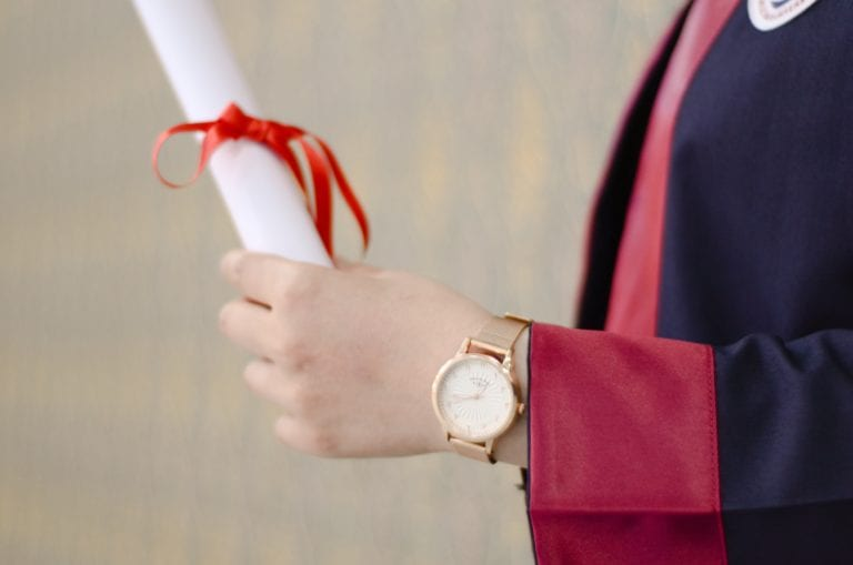 Graduate holding a diploma with a bow tied around it in her hand.