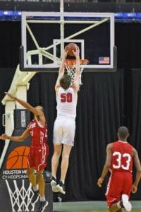 Offensive player dunks over defender.